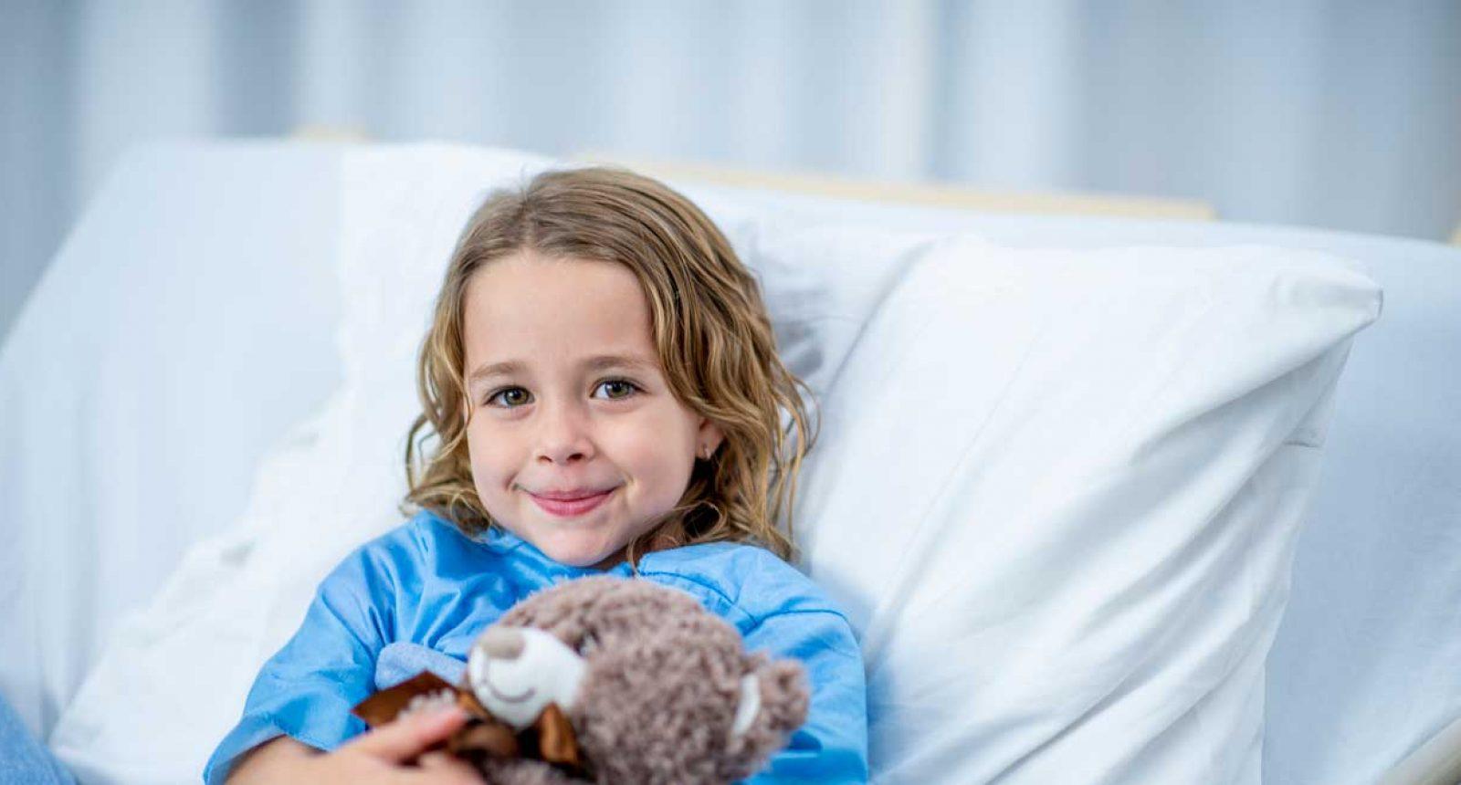 Jente i sykeseng med bamse